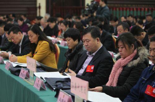 出席市十六届人大七次会议的代表聆听报告